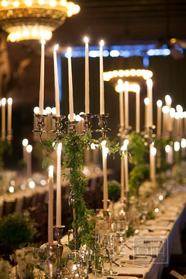 Decoración de las mesas de la boda con velas largas en un candelabro