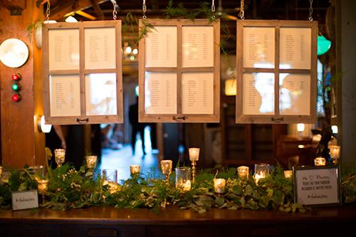 Tableros para asignar las mesas a los invitados con decoración de velas