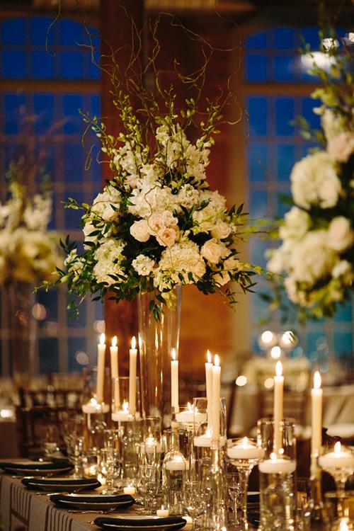 Velas sobre botellas de cristal para decorar las mesas de la boda