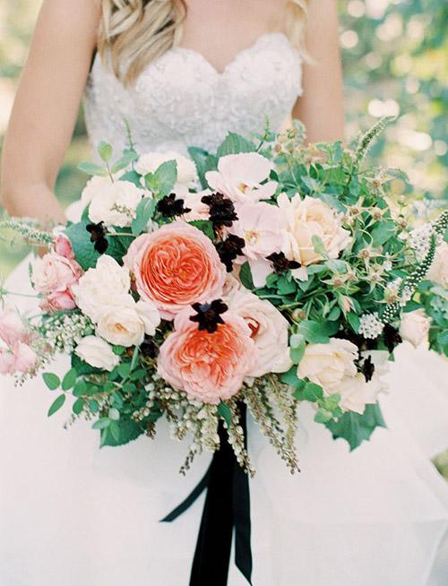 Flores blancas y coral en el ramo de la novia