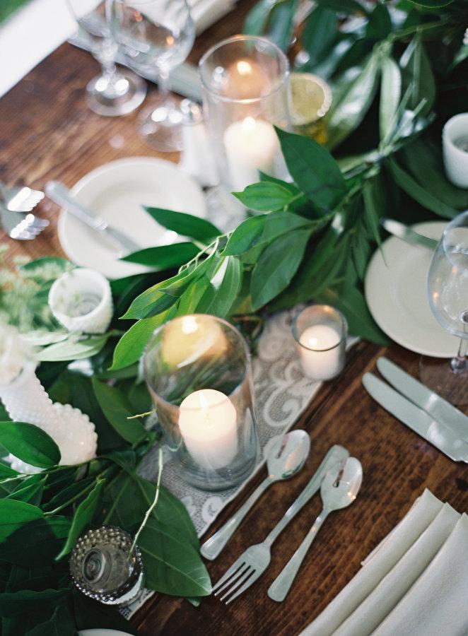 Mesas de invitados decoradas con hojas verdes y velas